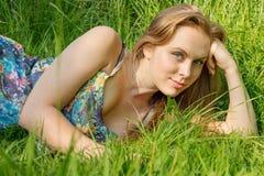 Ung kvinna med långt hår som ligger på gräset i sommar Royaltyfri Bild
