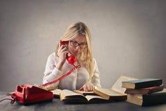 Ung kvinna med långt hårsammanträde i läsning för fönsterplats arkivbild