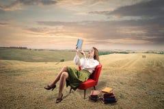 Ung kvinna med långt hårsammanträde i läsning för fönsterplats royaltyfri fotografi