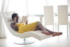 Ung kvinna med långt hårsammanträde i läsning för fönsterplats arkivfoto