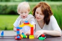Ung kvinna med litet barnsonen som spelar med plast- kvarter Arkivbilder