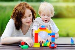 Ung kvinna med litet barnsonen som spelar med plast- kvarter Royaltyfria Foton
