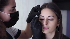 Ung kvinna med lockigt hår i svarta handskar som noppar hennes klientögonbryn i skönhetsalong Plocka för ung kvinna stock video
