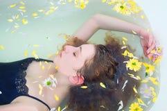 Ung kvinna med lockigt hår som tar ett bad med örter Royaltyfri Fotografi