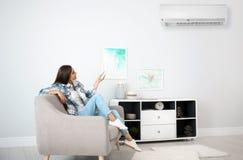 Ung kvinna med luftkonditioneringsapparatfjärrkontrollen royaltyfri fotografi