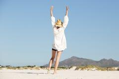 Ung kvinna med lyftta armar som går på stranden Fotografering för Bildbyråer