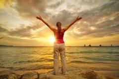 Ung kvinna med lyftta händer som står på kust och ser till a Royaltyfri Fotografi