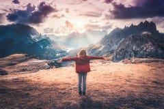 Ung kvinna med lyftta upp armar och berg på solnedgången arkivbilder