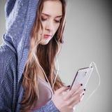 Ung kvinna med lyssnande musik för smart telefon Royaltyfri Foto