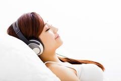 Ung kvinna med lyssnande musik för hörlurar Royaltyfri Bild