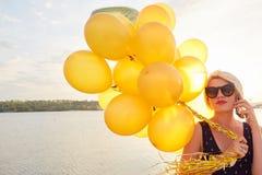 Ung kvinna med många guld- ballonger Royaltyfri Fotografi