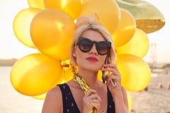 Ung kvinna med många guld- ballonger Fotografering för Bildbyråer
