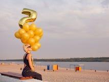 Ung kvinna med många guld- ballonger Royaltyfria Bilder