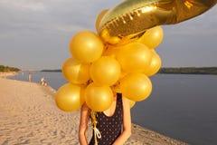 Ung kvinna med många guld- ballonger Royaltyfria Foton