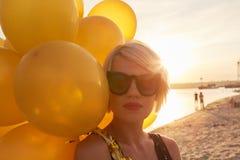 Ung kvinna med många guld- ballonger Arkivfoton