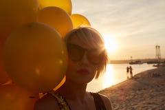 Ung kvinna med många guld- ballonger Royaltyfri Bild