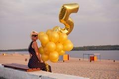 Ung kvinna med många guld- ballonger Royaltyfri Foto