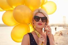 Ung kvinna med många guld- ballonger Arkivfoto
