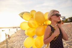 Ung kvinna med många guld- ballonger Arkivbild