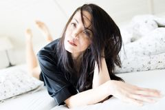 Ung kvinna med mörka hår i hennes framsida som lägger i säng i svart klä kappa royaltyfri fotografi