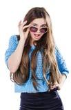 Ung kvinna med mörkt hår som bär ett blått stuckit tröjaanseende på en vit bakgrund med isoleringspunkterna Håll exponeringsglas Royaltyfri Bild