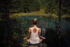 Ung kvinna med mehendi på hennes meditera tillbaka nära blå mounta Royaltyfri Bild