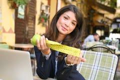 Ung kvinna med metern och äpplet Bekläda beskådar royaltyfri fotografi