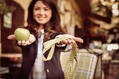Ung kvinna med metern och äpplet close upp arkivfoto