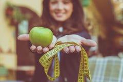 Ung kvinna med metern och äpplet Fokus på händer royaltyfria bilder