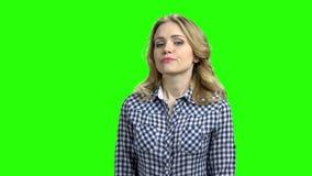 Ung kvinna med misstrogen blick på den gröna skärmen