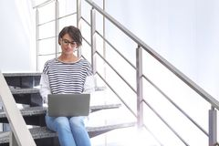 Ung kvinna med modernt bärbar datorsammanträde på trappa royaltyfria foton