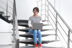 Ung kvinna med modernt bärbar datorsammanträde på trappa arkivbilder