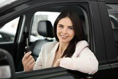Ung kvinna med nyckel- sammanträde i plats för chaufför` s av automatiskn Royaltyfria Foton