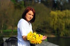 Ung kvinna med påskliljar Arkivbilder