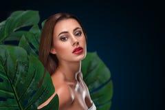 Ung kvinna med perfekt hud inom tropisk lövverk Royaltyfria Foton