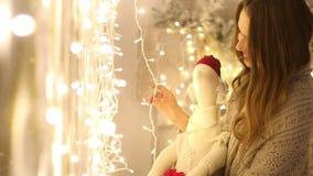 Ung kvinna med plädet och Santa Claus i hennes girland för ljusa kulor för för handleenden och handlag stock video