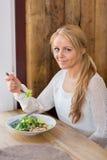 Ung kvinna med plattan av sallad i restaurang Royaltyfri Fotografi