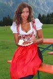 Ung kvinna med plommoncaken och kräm Fotografering för Bildbyråer