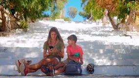 Ung kvinna med pojkesammanträde på trappa som ser smartphonen stock video