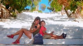 Ung kvinna med pojkesammanträde på trappa som ser smartphones arkivfilmer