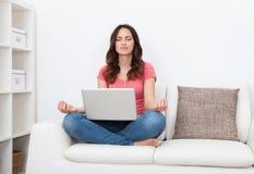 Ung kvinna med praktiserande yogasammanträde för bärbar dator på soffan Arkivfoto