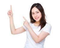 Ung kvinna med punkt för två finger upp Fotografering för Bildbyråer