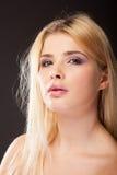 Ung kvinna med purpurfärgad makeup i studiofoto royaltyfria bilder