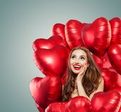 Ung kvinna med röd hjärta för ballonger Förvånad flicka med röd kantmakeup, lockigt hår och gulliga leendet som ser upp royaltyfri bild
