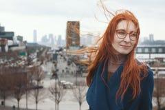 Ung kvinna med rött hår som är främst av New York horisont Arkivbild
