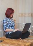 Ung kvinna med rött hår som hemifrån arbetar - den kvinnliga entreprenören Sitting på säng med bärbar datordatoren, Royaltyfri Fotografi