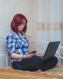 Ung kvinna med rött hår som hemifrån arbetar - den kvinnliga entreprenören Sitting på säng med bärbar datordatoren, Royaltyfri Bild