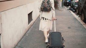 Ung kvinna med resväskan och ryggsäcken som går till och med byggnaden i staden Flicka med bagage som flyttar sig till det nya st Fotografering för Bildbyråer