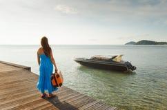 Ung kvinna med resväskan på pir Arkivbild