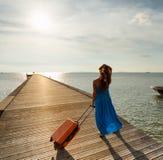 Ung kvinna med resväskan på pir Arkivbilder